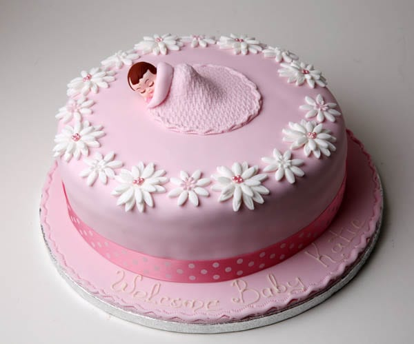 A pink baby girl themed cake with icing and baby fondant by Quigleys cafe bakery and deli