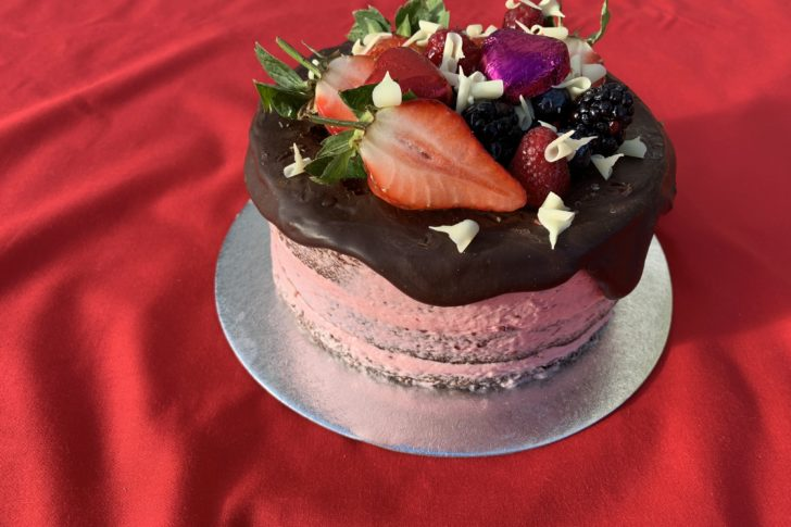 A round Valentines celebration cake with pink icing, chocolate top and fruit