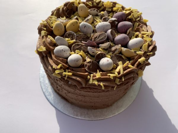 A round chocolate, mini eggs easter themed cake available to order from Quigleys bakery